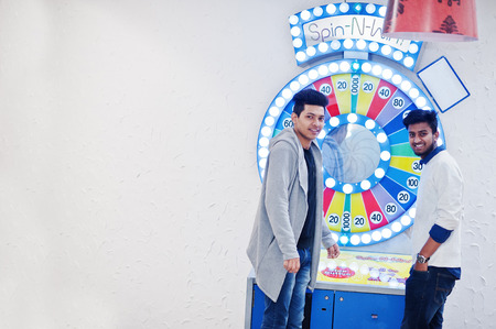 Two young asian guys play in fortune wheel to win at lottery big prize.