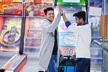 We are millionaires! Very excited two young asian guys against fortune wheel win at lottery big prize. Give high five each other. Imagens - 120997988