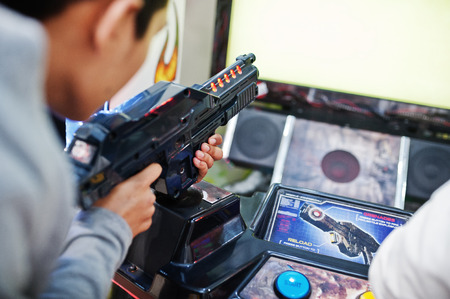 Two asian guys compete on shooter simulator game arcade machine.