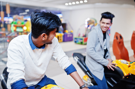 Two asian guys compete on speed rider arcade game motorcycle racing simulator machine. Imagens