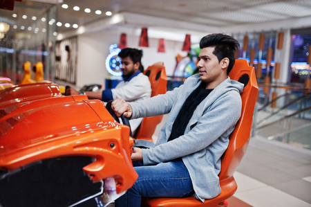 Two asian guys compete on speed rider arcade game racing simulator machine. Banco de Imagens