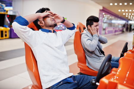 I'm loser!Two asian guys compete on speed rider arcade game racing simulator machine. Stockfoto
