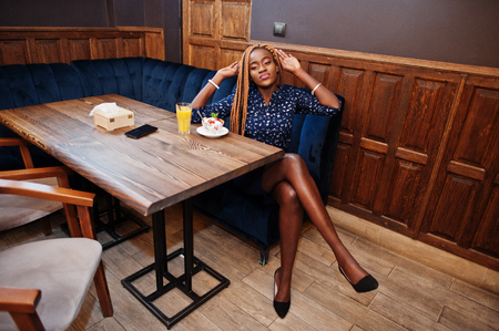 Portrait of beautiful young african business woman with dreadlocks, wear on blue blouse and skirt, sitting in cafe with ice cream and pineapple juice.