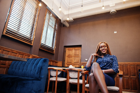 Portrait of beautiful young african business woman, wear on blue blouse and skirt, sitting in cafe. Foto de archivo