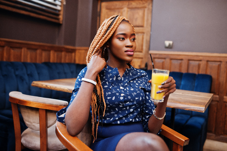 Portrait of beautiful young african business woman, wear on blue blouse and skirt, sitting with juice in cafe.