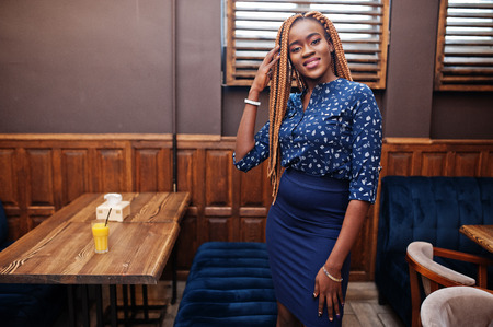 Portrait of beautiful young african business woman with dreadlocks, wear on blue blouse and skirt, posed in cafe.