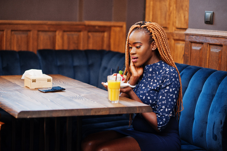 Portrait of beautiful young african business woman with dreadlocks, wear on blue blouse and skirt, sitting in cafe with ice cream and pineapple juice. Surprised face. Фото со стока