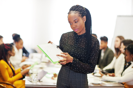 Face of handsome african business woman, holding clipboard on the background of business peoples multiracial team meeting, sitting in office table.