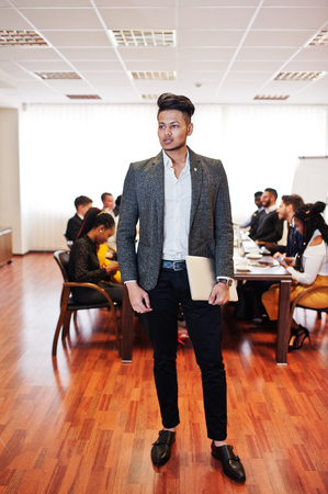 Face of handsome asian business man, holding laptop on the background of business peoples multiracial team meeting, sitting in office table.