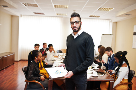 Face of handsome arabian business man, holding clipboard on the background of business peoples multiracial team meeting, sitting in office table. 스톡 콘텐츠