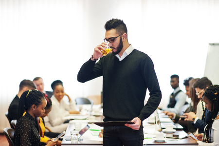Face of handsome arabian business man, holding clipboard and glasses of beverage on the background of business peoples multiracial team meeting, sitting in office table. 스톡 콘텐츠
