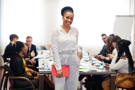 Face of handsome african american business woman, holding tablet on the background of business peoples multiracial team meeting, sitting in office table. 스톡 콘텐츠