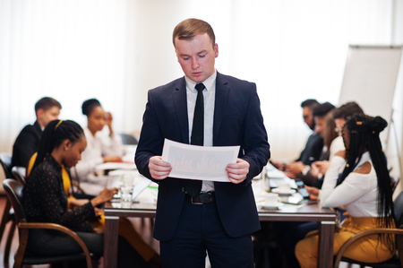 Face of handsome european business man, holding paper with diagram on the background of business peoples multiracial team meeting, sitting in office table. 스톡 콘텐츠