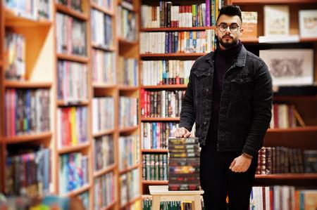 Hombre alto estudiante árabe inteligente, use chaqueta de jeans negros y anteojos, en la biblioteca con pila de libros.