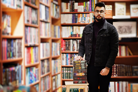Tall smart arab student man, wear on black jeans jacket and eyeglasses, at library with stack of books.