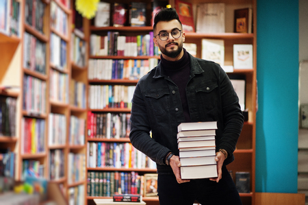Lange slimme arabische studentenman, draag een zwart spijkerjack en een bril, in de bibliotheek met een stapel boeken.