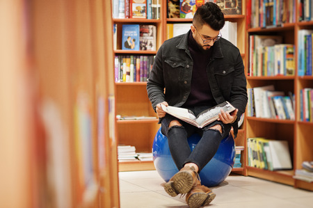 Tall smart arab student man, wear on black jeans jacket and eyeglasses, sitting at library and read book at hands. 版權商用圖片