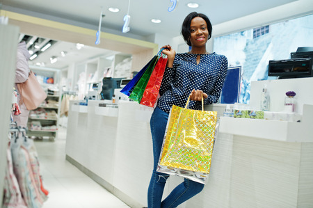 Happy african american woman customer with colored shopping bags paying near cash teminal.