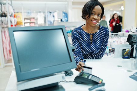 Happy african american woman customer with colored shopping bags paying by credit card near cash teminal with pos.