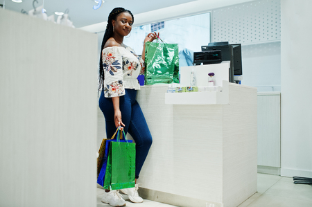 Happy african american woman customer with colored shopping bags paying near cash teminal. Stock Photo