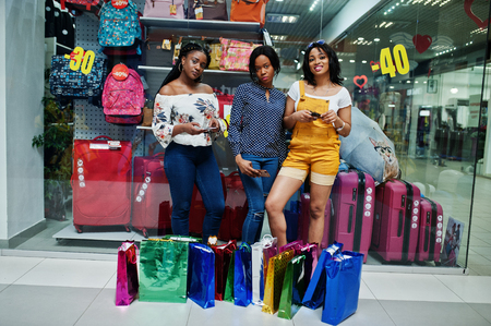 Beautiful three well-dressed afro american girls with colored shopping bags in mall against showcase of suitcase store with mobile phones at hands.