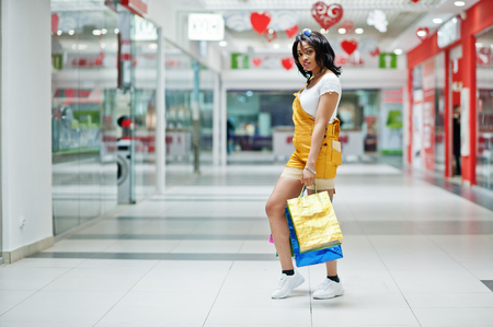 Beautiful well-dressed afro american woman customer with colored shopping bags at mall. Stock Photo