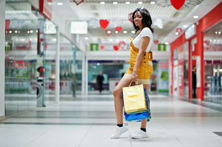 Beautiful well-dressed afro american woman customer with colored shopping bags at mall. 版權商用圖片