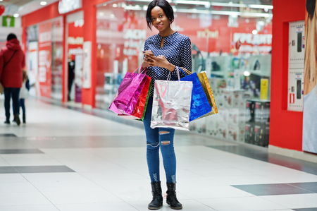 Beautiful well-dressed afro american woman customer with colored shopping bags, with mobile phone at hands in mall.