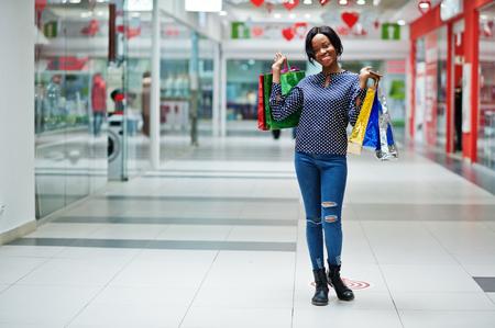 Cliente de hermosa mujer afroamericana bien vestida con bolsas de colores en el centro comercial.