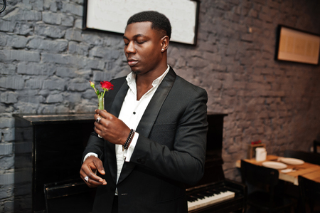 Strong powerful african american man in black suit sniff flower in test tube against piano.