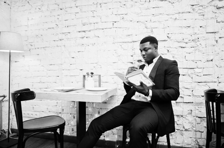 Strong powerful african american man in black suit sitting at cafe, read book and sniff flower in test tube.