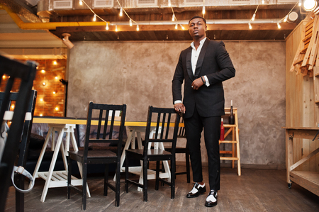 Strong powerful african american man in black suit posed in cafe. 版權商用圖片