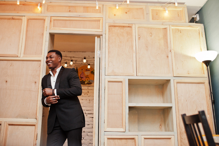 Strong powerful african american man in black suit posing against wooden bookcase.