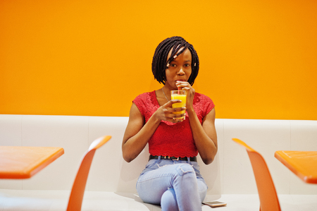 African woman sitting on cafe against orange wall and drink pineapple juice in hands.