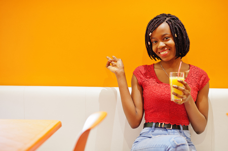 African woman sitting on cafe against orange wall with pineapple juice in hands, show two fingers. Imagens - 121405423
