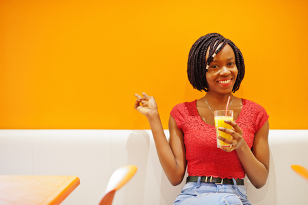 African woman sitting on cafe against orange wall with pineapple juice in hands, show two fingers. Archivio Fotografico