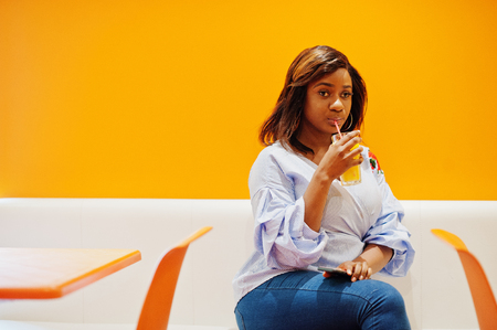 African woman sitting on cafe against orange wall drink pineapple juice in hands.