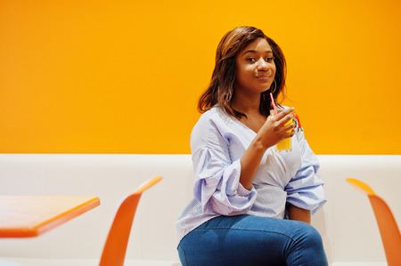African woman sitting on cafe against orange wall with pineapple juice in hands.