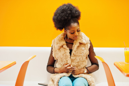 African woman with afro hair sitting on cafe against orange wall.