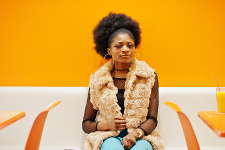 African woman with afro hair sitting on cafe against orange wall. Stock Photo