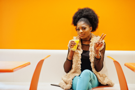 African woman sitting on cafe against orange wall with pineapple juice in hands and show two fingers.