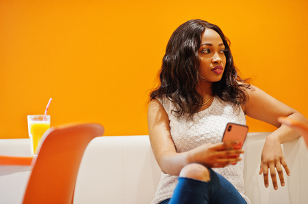 African woman sitting on cafe against orange wall with pineapple juice and hold phone at hand.