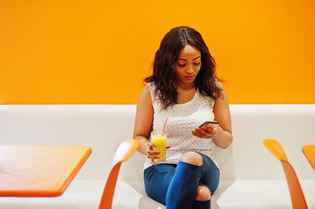 African woman sitting on cafe against orange wall with pineapple juice and mobile phone in hands.
