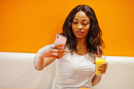 African woman sitting on cafe against orange wall with pineapple juice and mobile phone in hands, she making selfie.