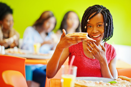 African woman with pizza sitting at restaurant against dark skinned girls.