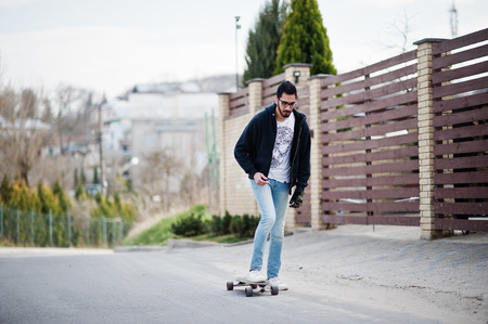 Street style arab man in eyeglasses with longboard longboarding down the road. Stock Photo