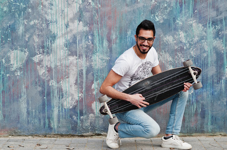 Street style arab man in eyeglasses with longboard posed against colored wall, like he play guitar. Stock Photo