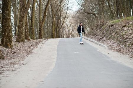 Street style arab man in eyeglasses with longboard longboarding down the road. Stock Photo