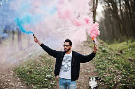 Street style arab man in eyeglasses hold hand flare with red and blue smoke grenade bomb.
