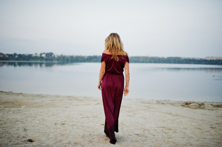 Back of blonde sensual barefoot woman in red marsala dress posing against lake.